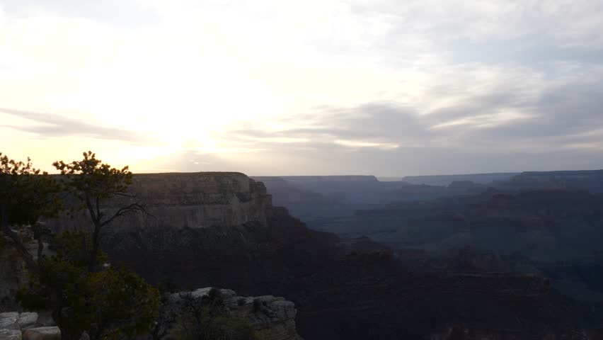 Dusk over the Grand Canyon from the southern rim with a glow on the horizon as the sun sinks from view behind distant mountains