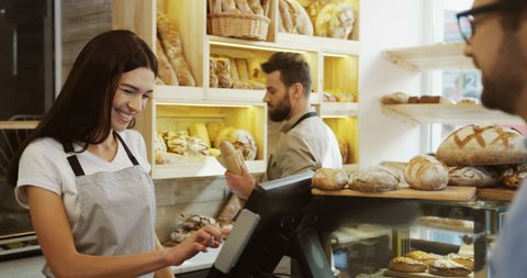 Young beautiful woman standing at the counter in the bakery shop and selling bread to the man, her male co-worker doing something behind her. Indoors