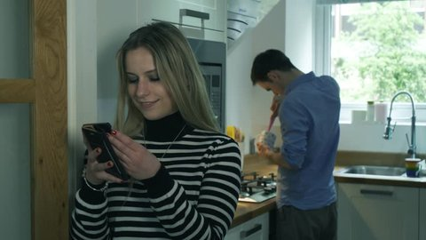Woman cheating and texting in kitchen partner unaware. Handheld of young girlfriend secretly texting another man whilst boyfriend cooks in background.