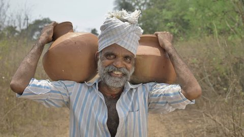 A happy and smiling male farmer carrying two earthen pots filled with freshwater on his shoulder in countryside. A cheerful middle aged man carrying two clay pots with a smile in rural or village area