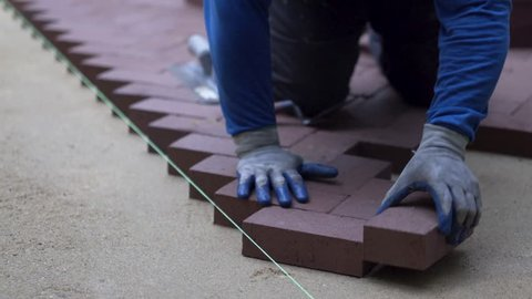 Using the butt of his trowel, a hardscaper taps the red brick pavers into place on a bed of sand.