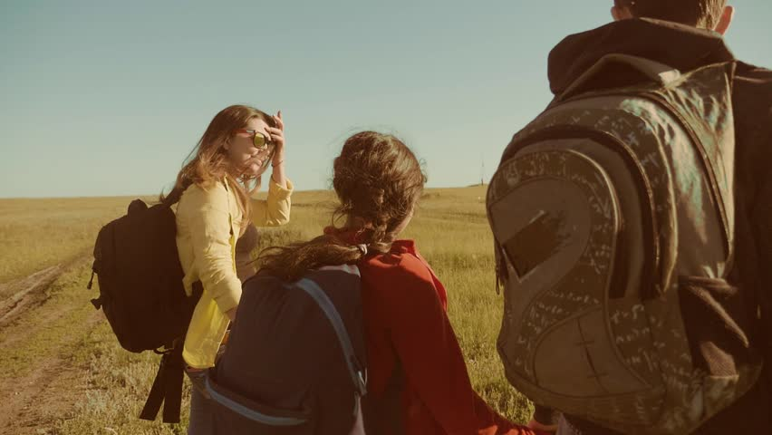 Happy family slow motion video walking on nature boy girl and mom in a field on trekking trip. tourists with backpacks traveling. lifestyle happy family travel tourism concept | Shutterstock HD Video #1011588086