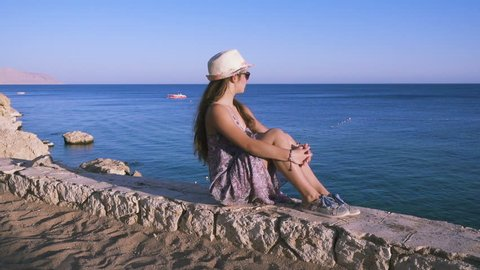 Young girl on the coast looking to azure sea, Sharm El sheikh, Egypt