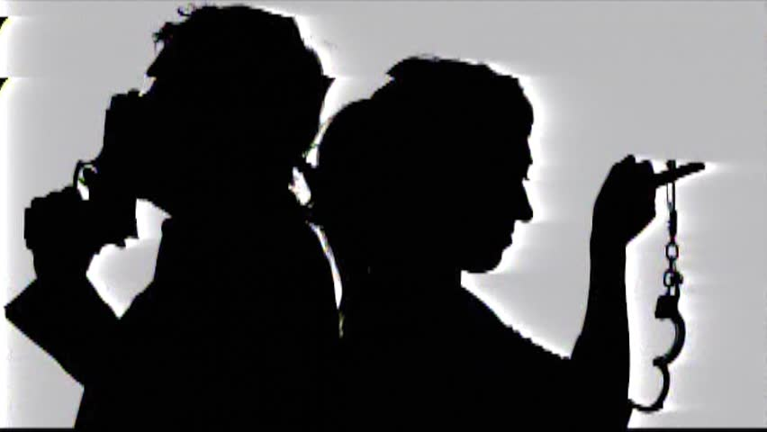 Analog capture (intentional heavy distortion fx): two detectives (a man and a woman) pulling out a gun and a pair of handcuffs. Silhouette shot.