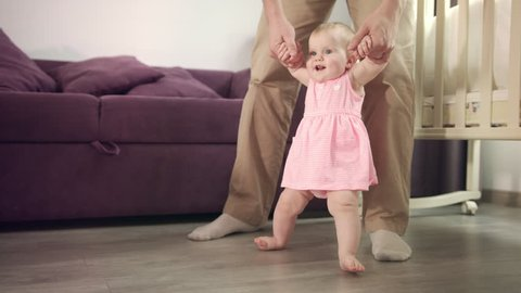 Beautiful baby girl stand up with father support. Infant learning walk. Child learning walk with daddy. First step in life. Sweet childhood. Happy family love. Parent care baby