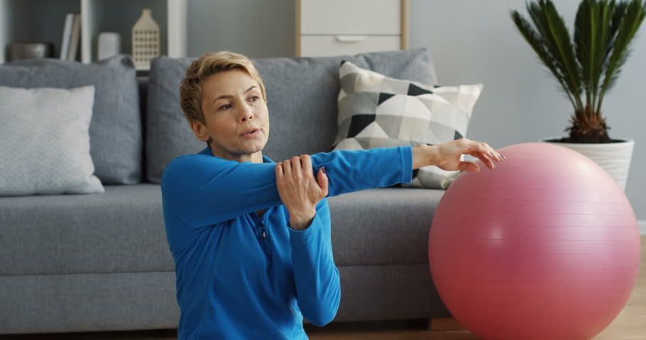 Sporty middle aged woman with short blond hair sitting in the living room and stretching her arms. Indoor | Shutterstock HD Video #1011650696