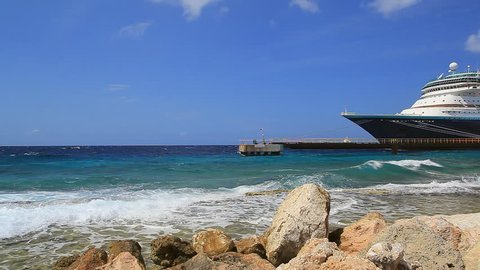 Coastline of Caribbean island with cruise ship in port on sunny day