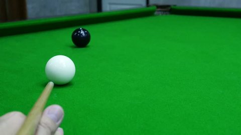 Slow motion of man playing snooker hit a black target ball into the corner pocket - snooker sport closeup concept