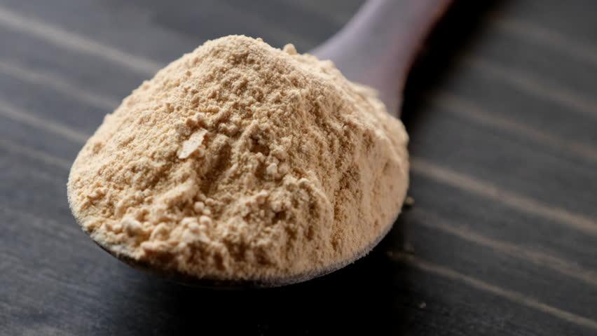 Rotating maca powder in wooden spoon.