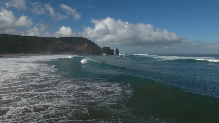 Aerial view of large surf waves breaking at Piha Beach, New Zealand