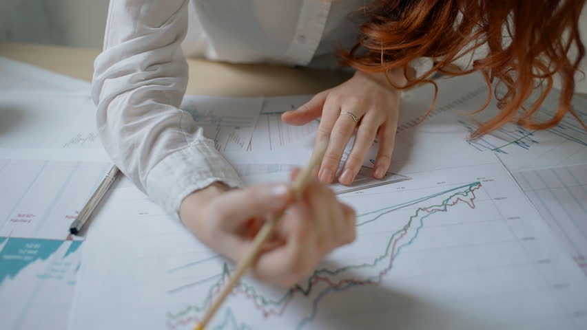 Young businesswoman is in working process with blueprint, sitting in comfortable workplace, attractive female in white shirt examining financial documents in office interior. Concept: analyzing work