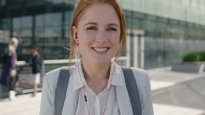 Close up portrait of happy redhead business woman intern wearing earphones listening to music laughing cheerful enjoying corporate career in city success achievement | Shutterstock HD Video #1011711776