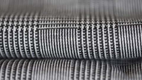 Super macro closeup shot of elegant houndstooth pied de poule fabric folded and laid on a clothing store or in a tailor's. Fashion concept.
