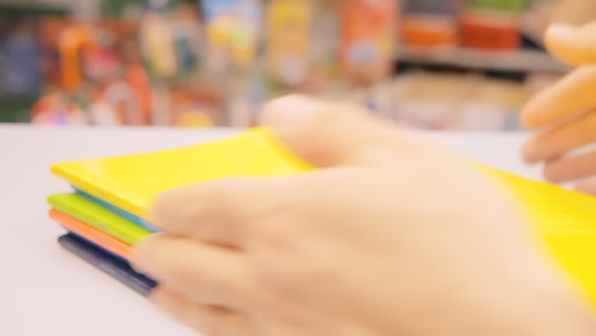 The hands of a stationery shop owner arranging and aligning a bunch of colorful notebooks.  | Shutterstock HD Video #1011727946
