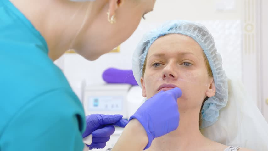 The hands of a plastic surgeon draw contours on the patient's face. 4k. for the procedure of contour plasty of the face. | Shutterstock HD Video #1011728126