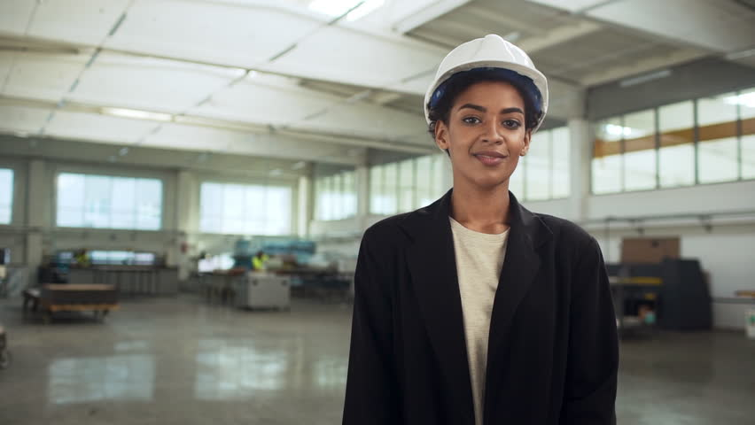 Portrait of successful african american woman in helmet and suit standing with arms crossed in big bright room of manufacture slow motion