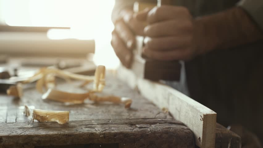 Professional skilled carpenter planing wood using a planer, woodworking and craftmanship concept