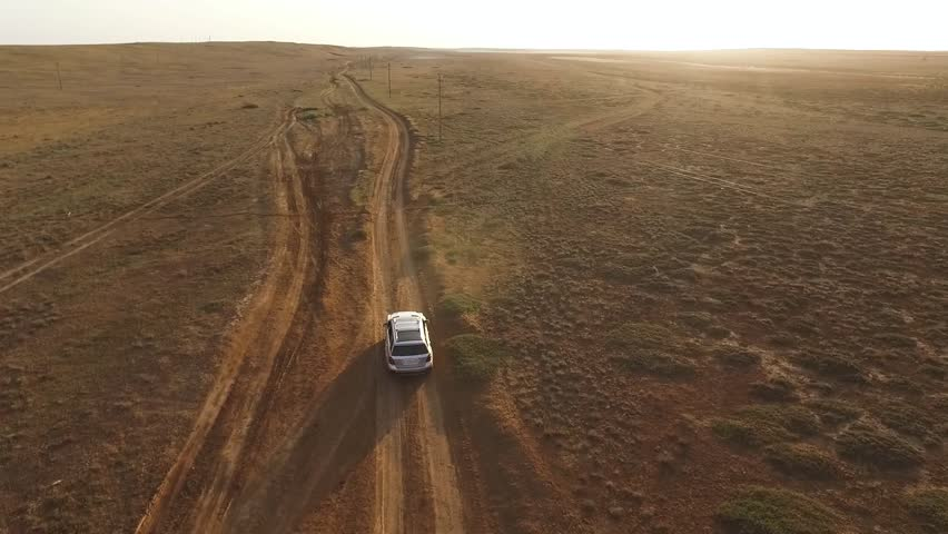 Back aerial view: Big silver SUV driving in a steppe in front of the sunset. #1011744686