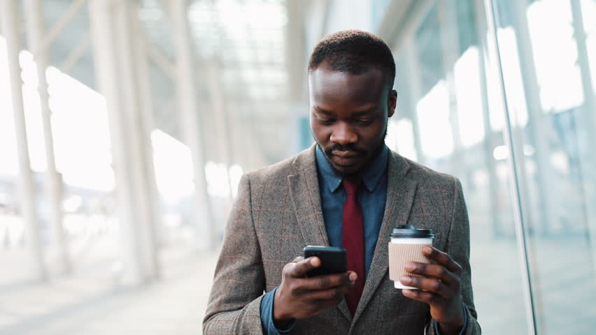 Young African Americanman using app on smartphone in city near the office center Handsome young businessman using smartphone smiling happy. #1011748196