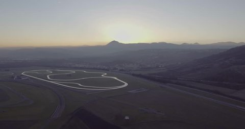Aerial shot / Drone shot of French test track sunrise, landscape with a morning sunrise of a French test track and fields, drone moves from wide shot of track including the motorway in the frame