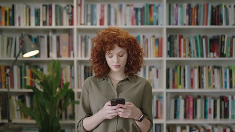 portrait of lovely young librarian woman standing in library attractive student smiling close up red head using smartphone