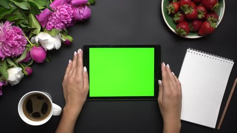 Woman working on tablet computer device with green screen. Beautiful white and pink peonies flowers, strawberries, coffe and notebook on the black background. Table top view. Chroma key