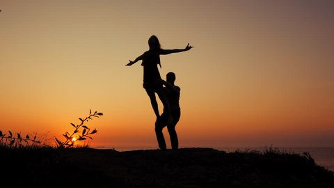 Beautiful sillhouettes of beautiful couple practicing in acro-yoga on the sea or ocean beach at sunset background, slow motion. Romantic scene. Healthy lifestyle, sport concept.