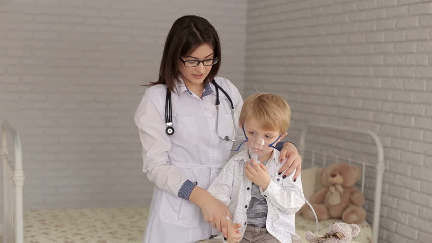 Pediatrics doctor hold a mask vapor inhaler to a little boy breathing through a steam nebulizer. The doctor and the child with inhalation mask showing thumb up, portrait.