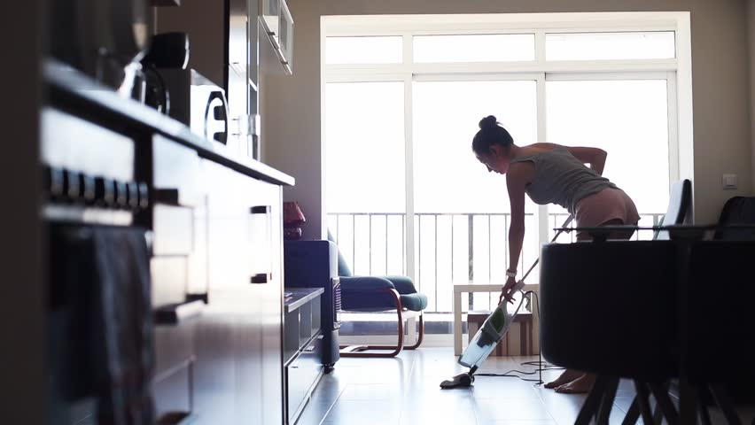 Young attractive sexy housewife vacuuming tile in the room. Woman cleaning her flat studio. | Shutterstock HD Video #1011765776