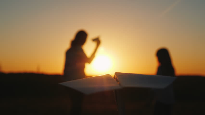 A happy family plays with paper airplanes. First-person view - in the foreground the plane flies, on the plane the woman and the child are having fun | Shutterstock HD Video #1011770906