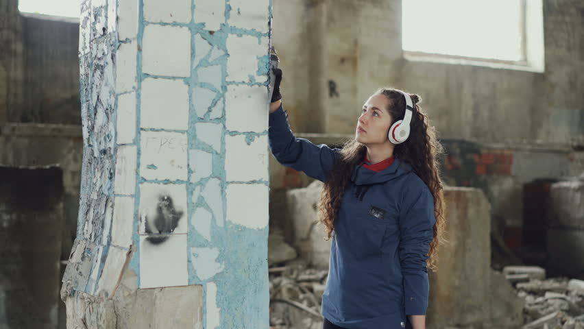 Attractive girl is concentrated on decorating old dirty column with graffiti in abandoned building using aerosol paint. Young woman is listening to music with headphones. #1011811166