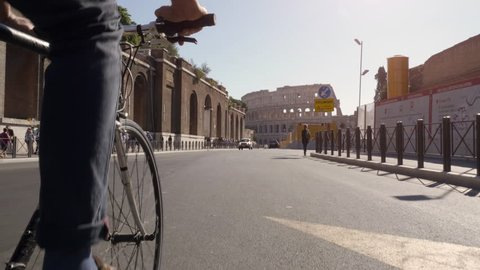 Young hipster man riding bike in roman forum imperial towards colosseum in Rome city centre on sunny day slow motion steadycam