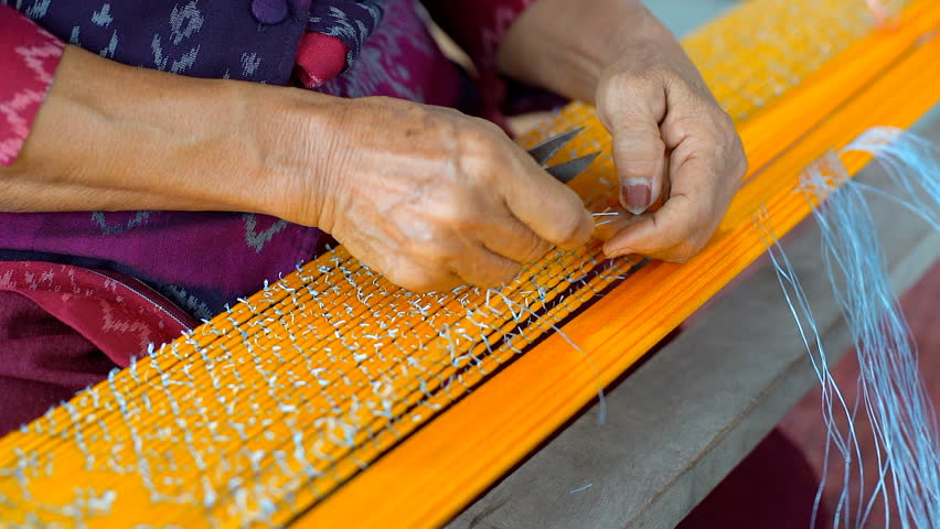 Thai Woman Making Ties Mudmee Board Weaving or Ikat Thai Silk Pattern Weaving on Small Red Weaving Mill Before Bring to Tie and Dyed in Thailand