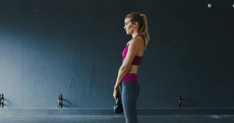 Beautiful athletic woman exercising with kettlebell in the gym