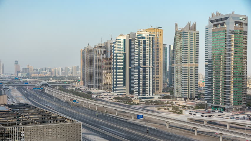 Amazing rooftop view on Sheikh Zayed road surrounded Dubai Marina and JLT skyscrapers, Dubai. Aerial view during sunset with traffic and metro line. United Arab Emirates