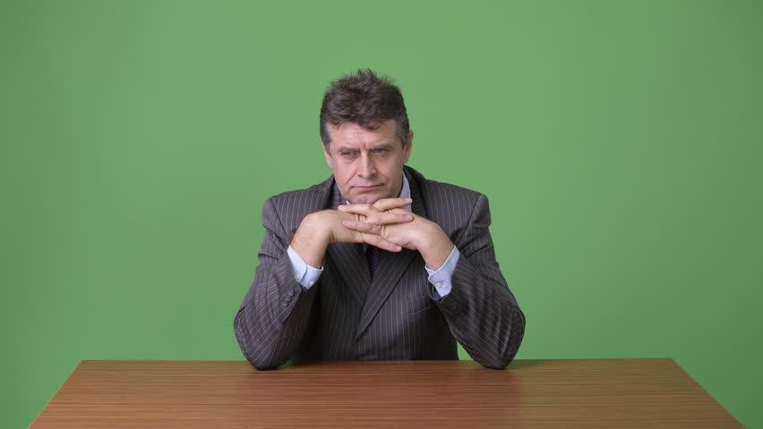 Mature handsome businessman against green background | Shutterstock HD Video #1011875096