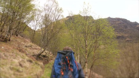 4K Young traveller hiking through the Scottish Highlands. Man path walking and back packing trekking through hilly natural landscapes of mountains and trees with bag. British hiker travelling