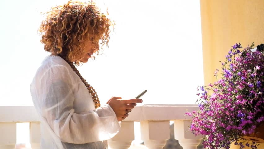 nice beautiful caucasian woman middle age use smartphone and take coffee outdoor in a sunny day of daily life. curly hair moved by the wind