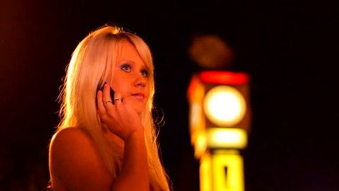 Sexy pretty blonde girl in red dress is speaking on phone. Outdoor, night city. Dissatisfied girl is waiting man on a date, but he is late