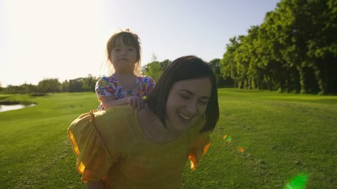 Laughing little toddler girl with down syndrome riding mother's back while mom is running on green grass meadow outdoors in summer. Mom giving piggyback ride to happy daughter in park. Steadicam shot