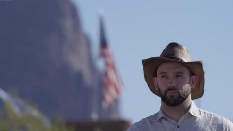 Cowboy man in front of flag and mountains