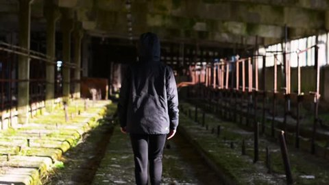 The girl  walking in abandoned building through the hallway. Back view horror dark mood. Steadicam shot. Smooth tracking. Old abandoned place.