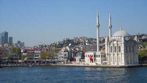ISTANBUL, TURKEY - APRIL, 24, 2018: Sailing near Ortakoy Mosque on bank of Bosphorus in Istanbul