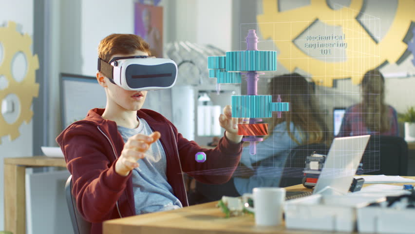 In a Computer Science Class Boy Wearing Virtual Reality Headset Works in Interactive 3D Environment. Mechanical Modeling Project of Connecting Gears with Augmented Reality Software. 4K UHD.   Shutterstock HD Video #1011929096