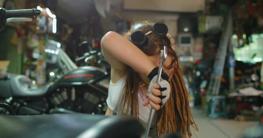 A stylish female biker makes maintenance of her motorcycle in the garage. She is tired and wipes the sweat from her forehead. tracking shot. in slow motion | Shutterstock HD Video #1011934796