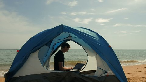 Freelancer Man Working Using Laptop Sitting In A Camping Tent On The Beach. Freelancer working on new startup project using laptop computer and wireless connection. Freelance Summer Travel