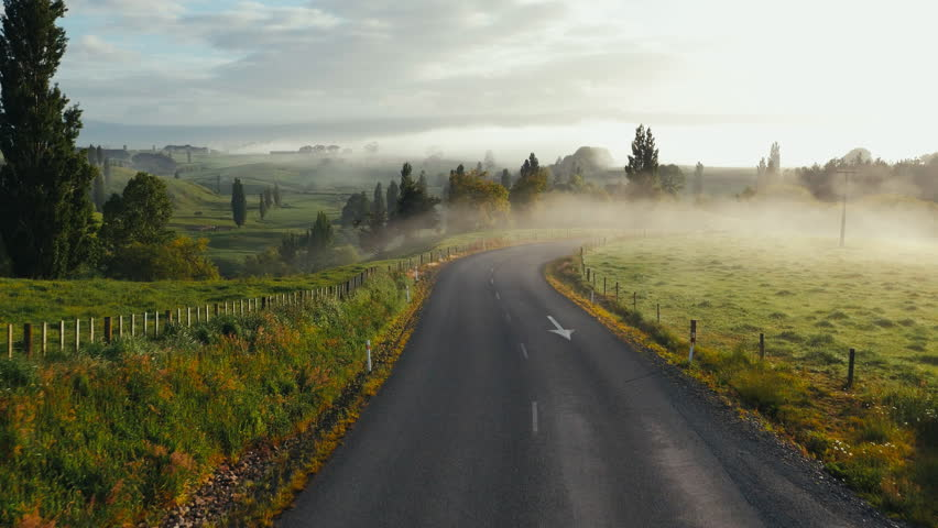 Dynamic drone shot following New Zealand country road at sunrise. Mysterious low hanging cloud over countryside.