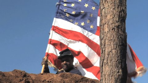 """VIRGINIA - JUNE 2017 - Reenactment - Civil War 54th Massachusetts Black Soldier stands tall on earthworks with U.S. Flag after battle. """"Glory"""" movie.  African-American military history. Heroic"""