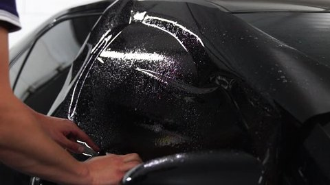 Master installs tint film for car glass with hairdryer and spatula with glare of light. Concept tinting