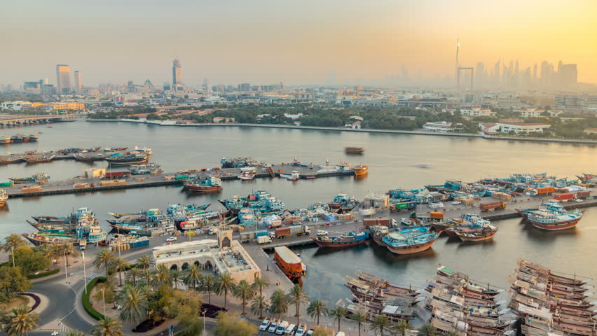 Dubai creek landscape timelapse with boats and ship in port, calm water and modern buildings with downtown skyscrapers in the background during sunset. Aerial top view from above